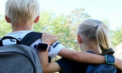 A young boy and girl wearing smartwatches.